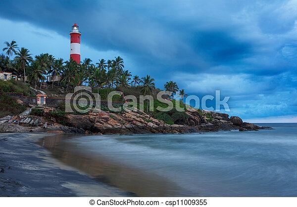 Gathering storm on beach and Kovalam (Vizhinjam) lighthouse on stormy sunset. Kerala, India - csp11009355