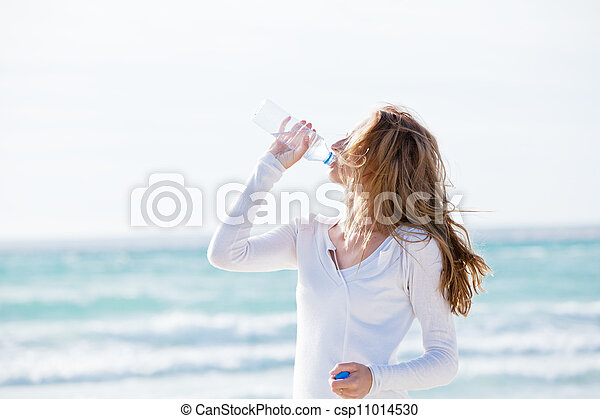 beautiful young woman drinking water in summer