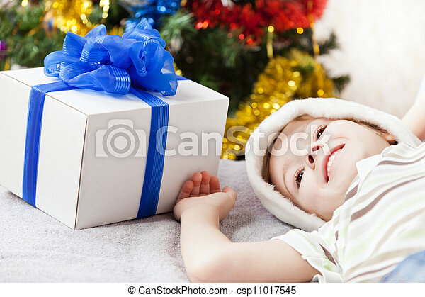 Cute smiling child boy in Santa Claus hat with new year present or christmas holiday gift box - csp11017545