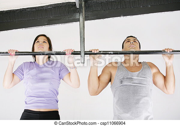 Young adult fitness woman and man preparing to do pull ups in pull up bar. - csp11066904