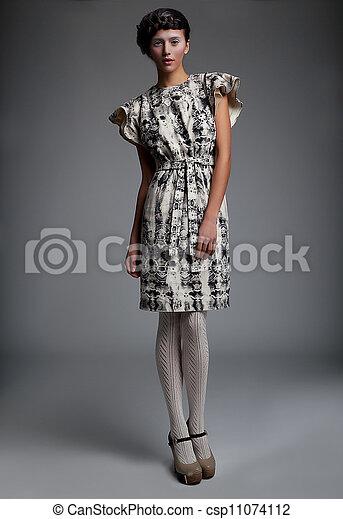 Fashion model pretty girl in retro dress standing in studio - csp11074112