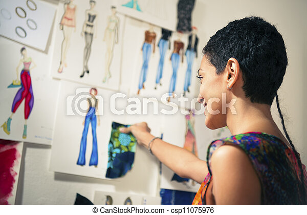 Female fashion designer contemplating drawings in studio - csp11075976