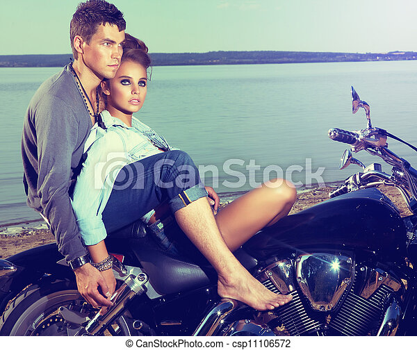 Romantic couple family resting on lake shore - motorbike - csp11106572