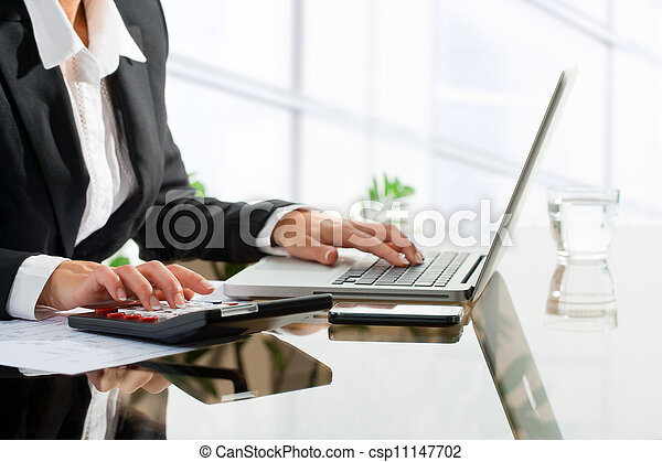 Female office worker doing accounting with calculator. - csp11147702