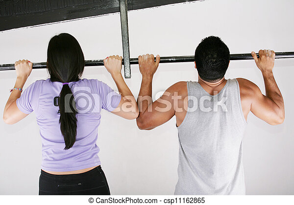 Young adult fitness woman and man preparing to do pull ups in pull up bar - csp11162865