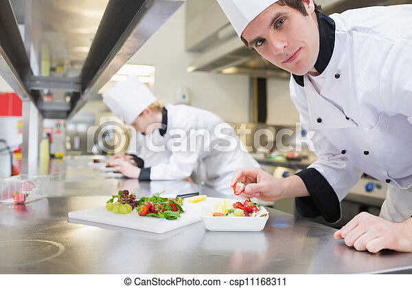 Man chef putting a strawberry in fruit salad - csp11168311