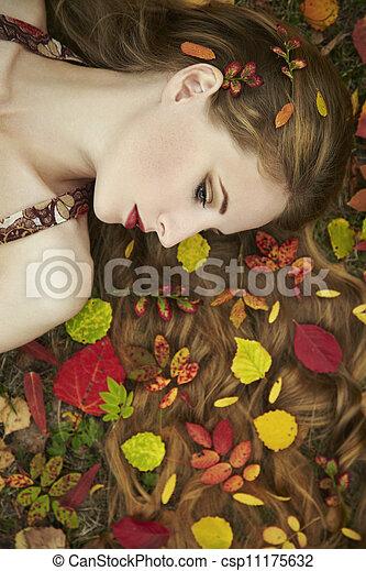 Fashion portrait of a beautiful young woman in autumn garden - csp11175632