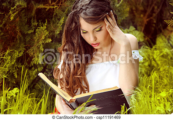 Young beautiful girl reading a book on green background of city