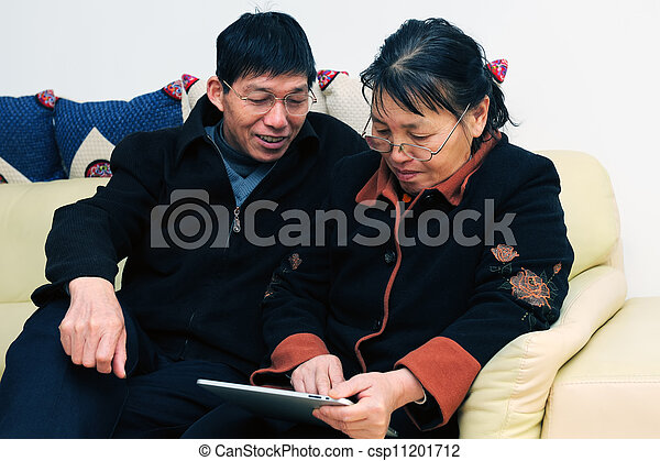 Asian elder couple playing with touchscreen tablet - csp11201712
