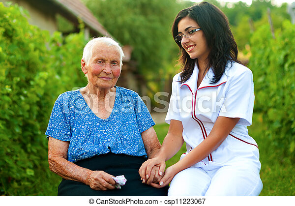 Caring doctor with sick elderly woman outdoors - csp11223067