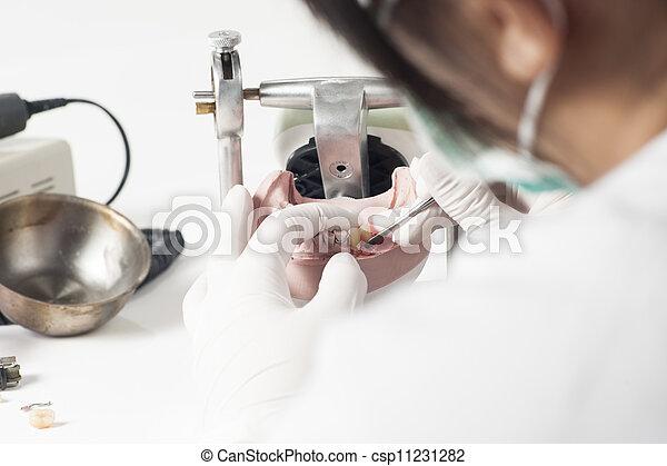Dental technician working with articulator - csp11231282
