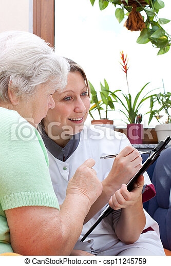 Senior and nurse sit together and write data - csp11245759