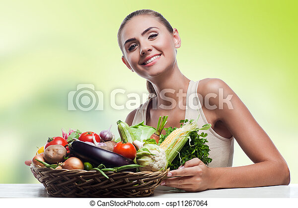 Happy young woman holding basket with vegetable. Concept vegetarian dieting - healthy food - csp11267064