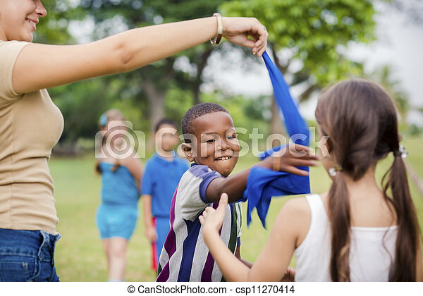 Children and teacher playing games in city park - csp11270414