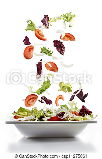 salad with fresh vegetables falling on plate - csp11275061