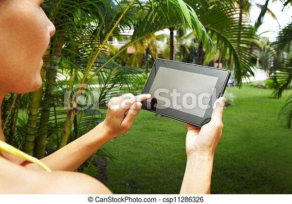 Hands with tablet computer in tropical garden. - csp11286326