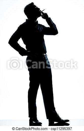 silhouette man full length smoking cigarette - csp11295397