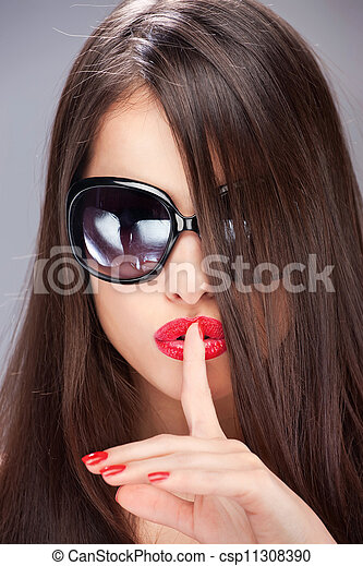 woman showing the sign for silence with her index finger - csp11308390