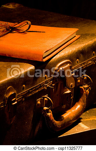 old, vintage, antique leather suitcase with leather bound and tied book on top painted with warm light - csp11325777