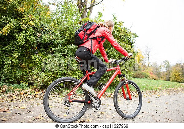Woman cyclist riding a bike in autumn park - csp11327969