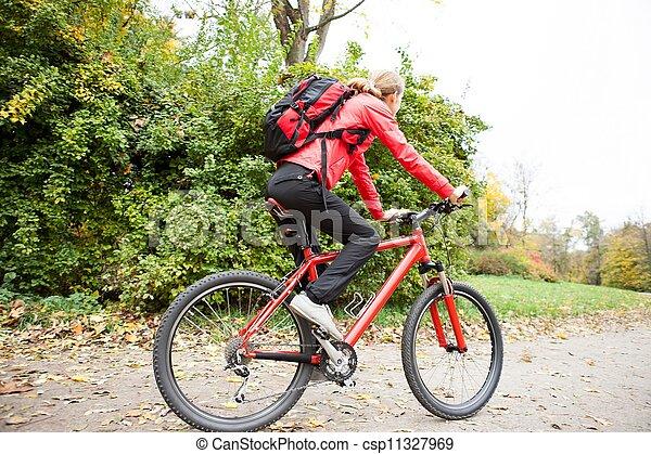 Woman cyclist riding a bike in autumn park - csp11327969