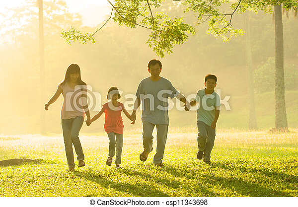 an asian family walking in the park during a beautiful sunrise, backlight - csp11343698