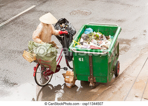 DA LAT, VIETNAM - 28 JULY 2012: Government worker separates the waste on the street for recycling. Pollution is a big problem in Vietnam nowadays. Da Lat, Vietnam, 28 JULY 2012 - csp11344507