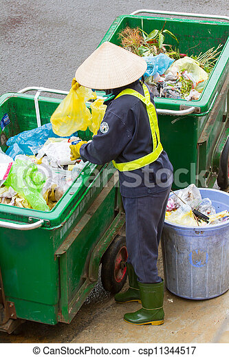 DA LAT, VIETNAM - 28 JULY 2012: Government worker separates the waste on the street for recycling. Pollution is a big problem in Vietnam nowadays. Vietnam, 2012 - csp11344517