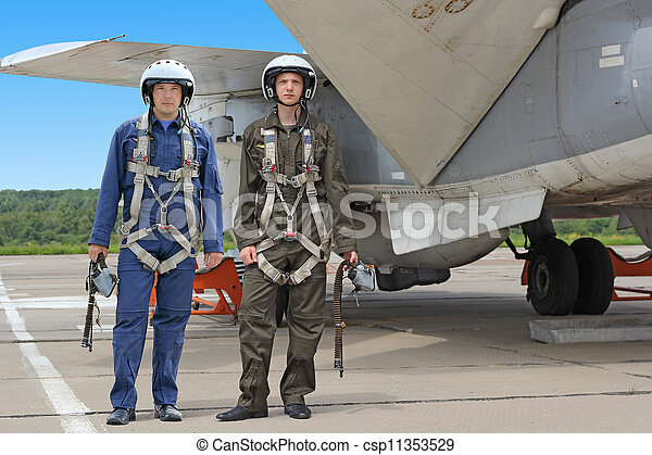 Two military pilot in a helmet near the aircraft - csp11353529