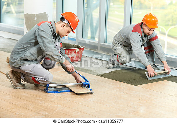 Two tilers at industrial floor tiling renovation - csp11359777