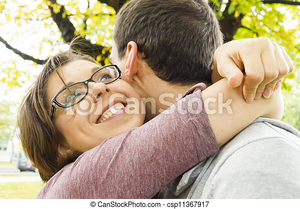 Portrait of love couple embracing outdoor in park looking happy - csp11367917