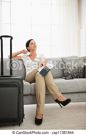 Dreaming woman with passport and air ticket sitting on sofa