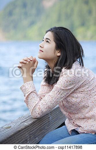 Young teen girl sitting quietly on lake pier, praying - csp11417898