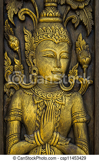 Buddha carved gold paint on church door - csp11453429