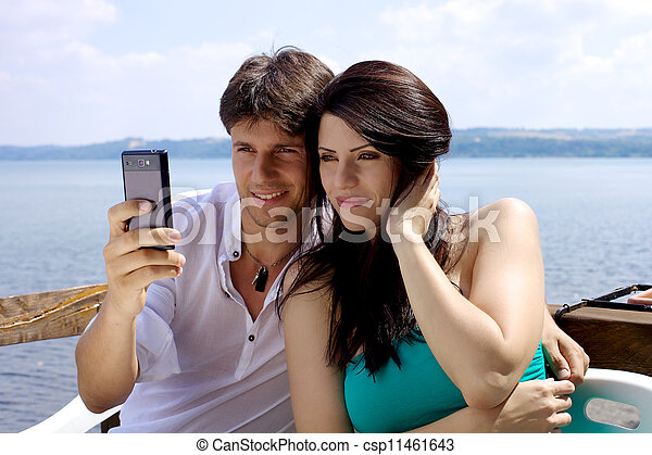 Beautiful man and woman taking picture in front of lake - csp11461643