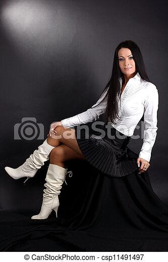 banque de photographies de mode jeune femme blanc chemise bottes noir jupe csp11491497. Black Bedroom Furniture Sets. Home Design Ideas