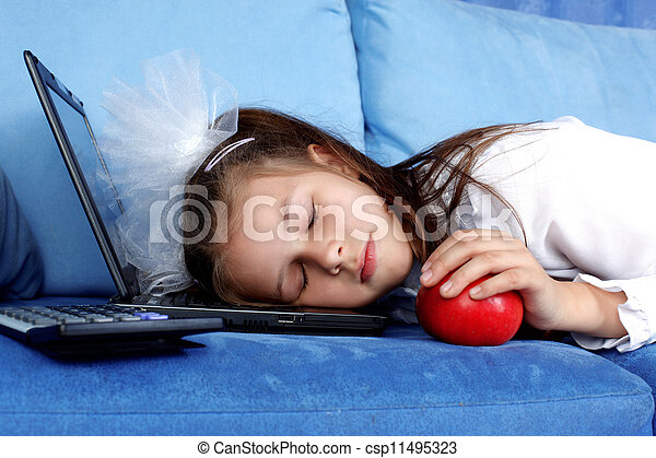tired girl sleeping at laptop with red apple