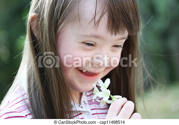 Portrait of beautiful young girl with flowers in the park - csp11498514