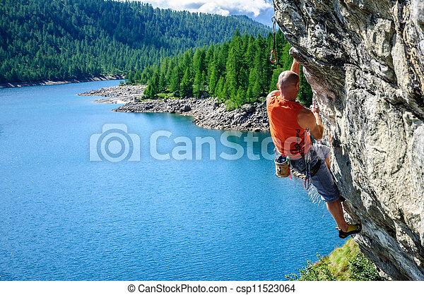 Climber climbing a rock wall above Lake Devero, Northern Italy - csp11523064