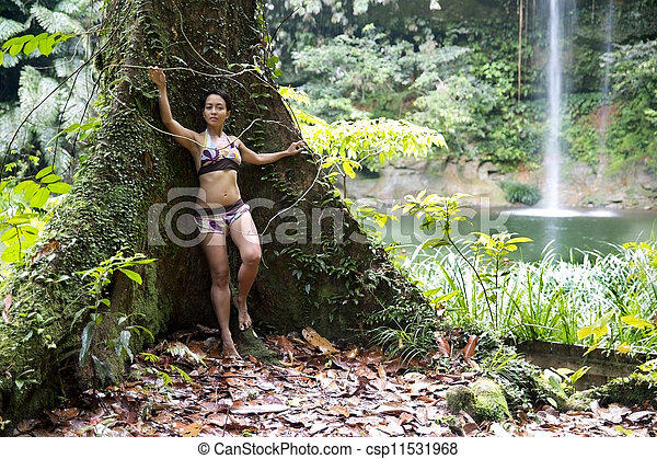 Sexy girl leaning huge tree in rainforest background waterfall - csp11531968