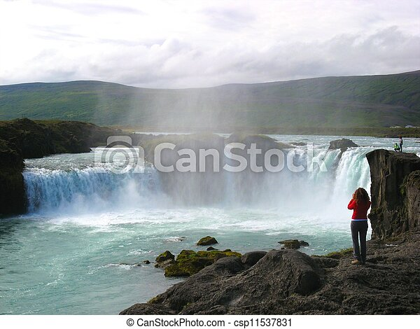 Wide angle shot of the famous Godafoss waterfall on Iceland, with excited tourists standing on the rocks taking photos - csp11537831