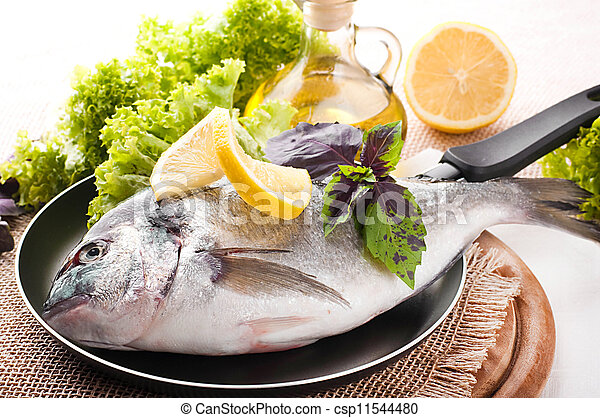 Pictures of fresh fish of dorado on a frying pan with a for Frying fish in olive oil