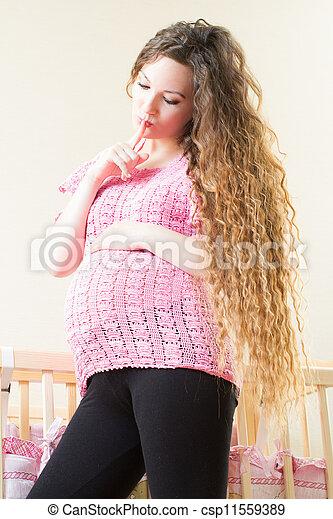 Pregnant woman with long hair near crib