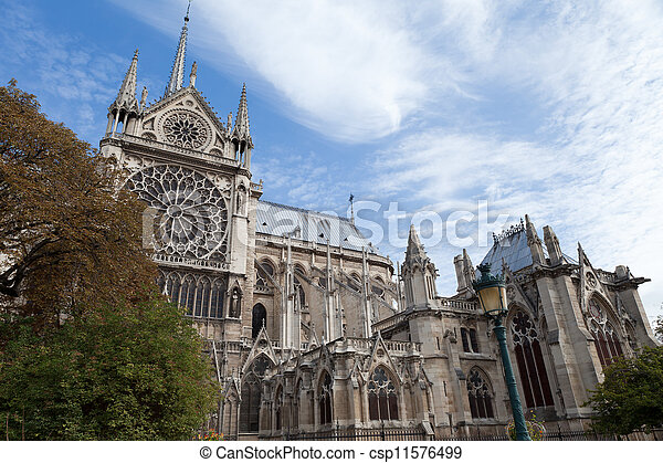 Famous landmark Gothic catholic cathedral Notre-dame on Cite island in Paris France on the blue and cloudy sky background - csp11576499
