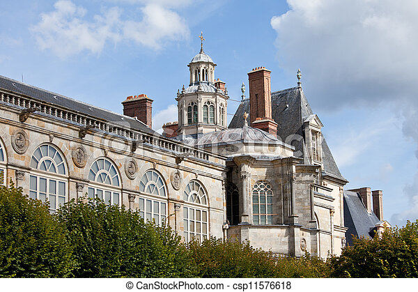 Medieval landmark royal hunting castle Fontainbleau near Paris in France and garden on the cloudy sky background - csp11576618