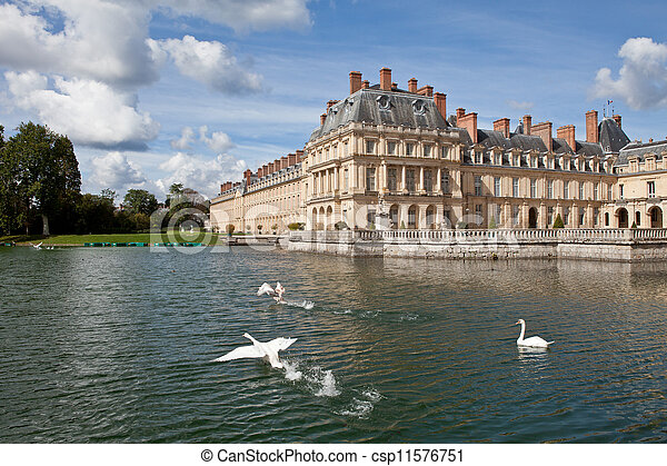 Medieval landmark royal hunting castle Fontainbleau near Paris in France and lake with white swans - csp11576751