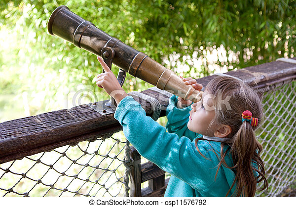 Little inquisitive girl preschooler discovers surroundings on observation balcony in spring park through old-style telescope and point a finger at finding - csp11576792