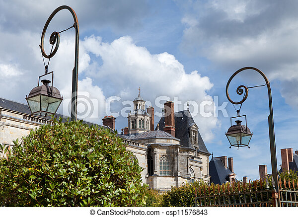 Medieval landmark royal hunting castle Fontainbleau near Paris in France and garden on the cloudy sky background - csp11576843
