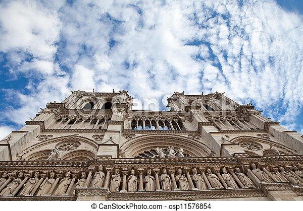 Famous landmark Gothic catholic cathedral Notre-dame on Cite island in Paris France on the blue and cloudy sky background - csp11576854