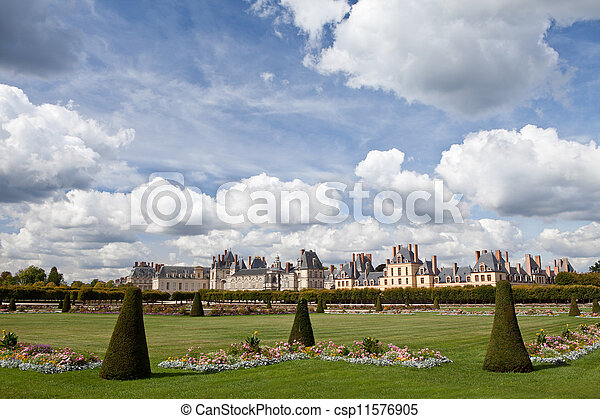 Medieval landmark royal hunting castle Fontainbleau near Paris in France and garden with flowers on the cloudy blue sky background - csp11576905